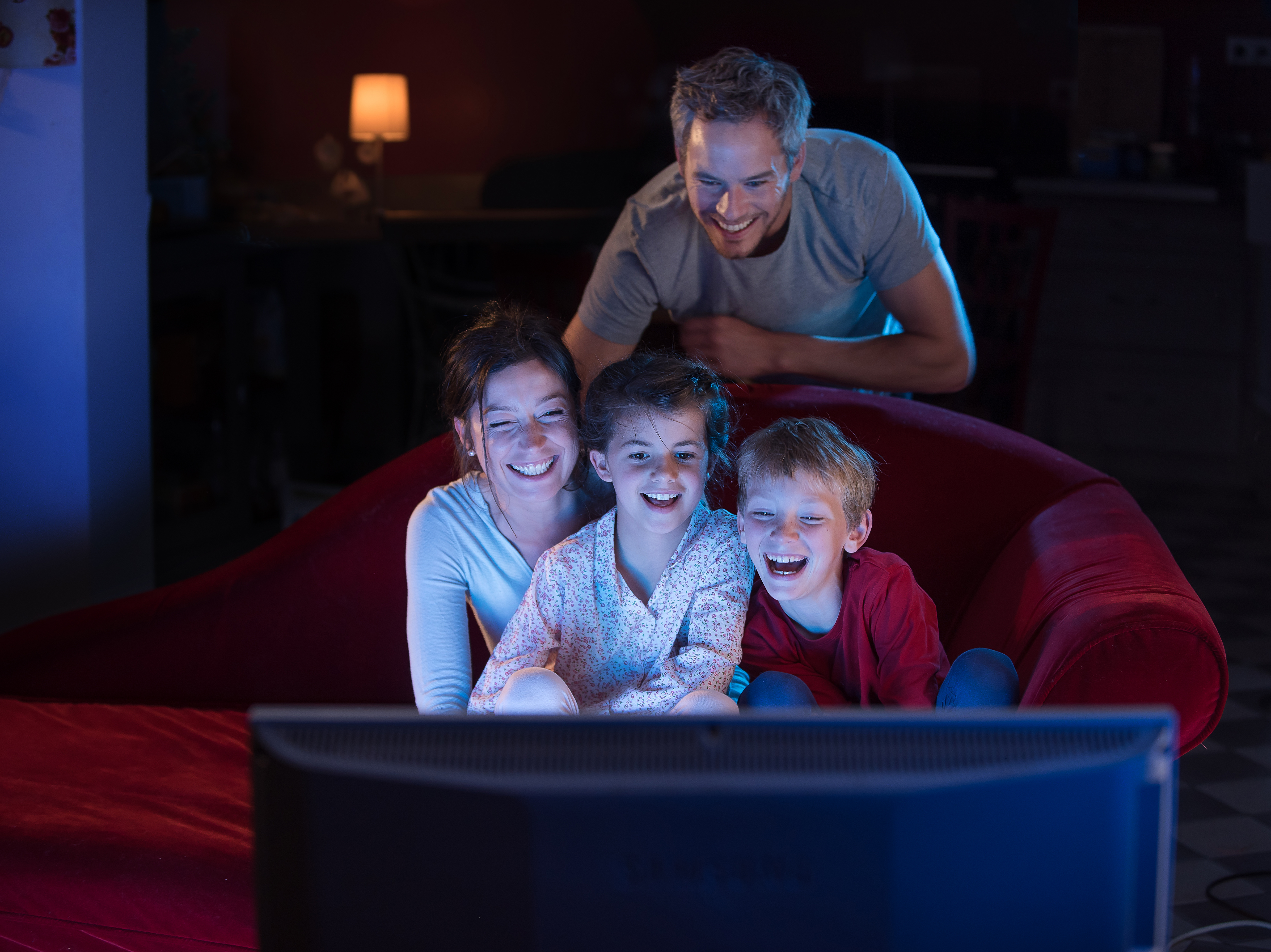 At home by night, a family watching a funny movie on tv.